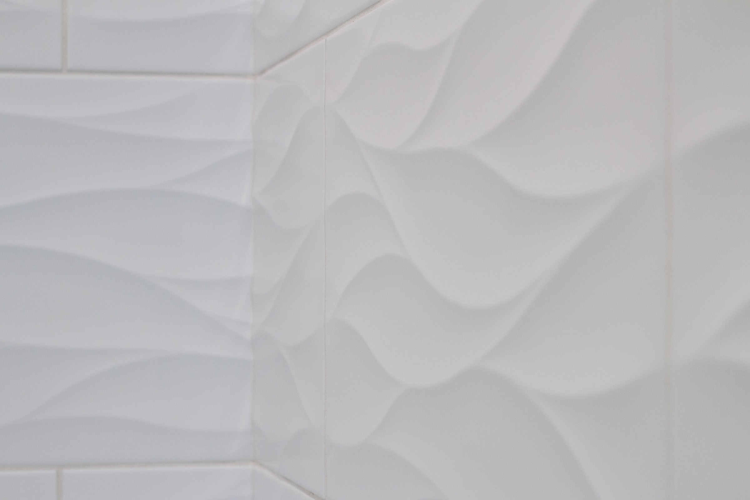Close up of white shower tile with wavy texture