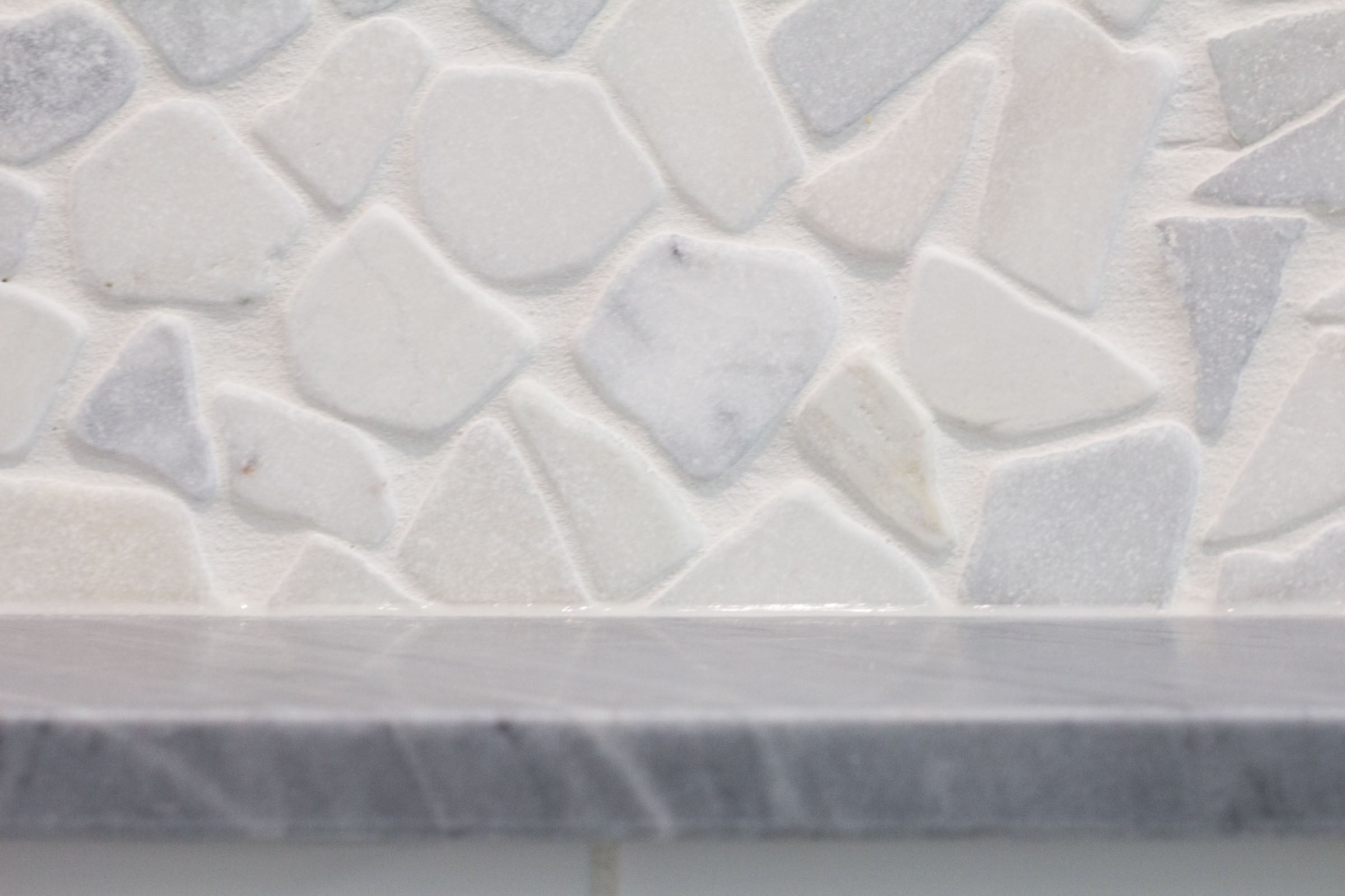 Close up shot of bathroom remodel with grey granite and multicolor pebble backsplash tile