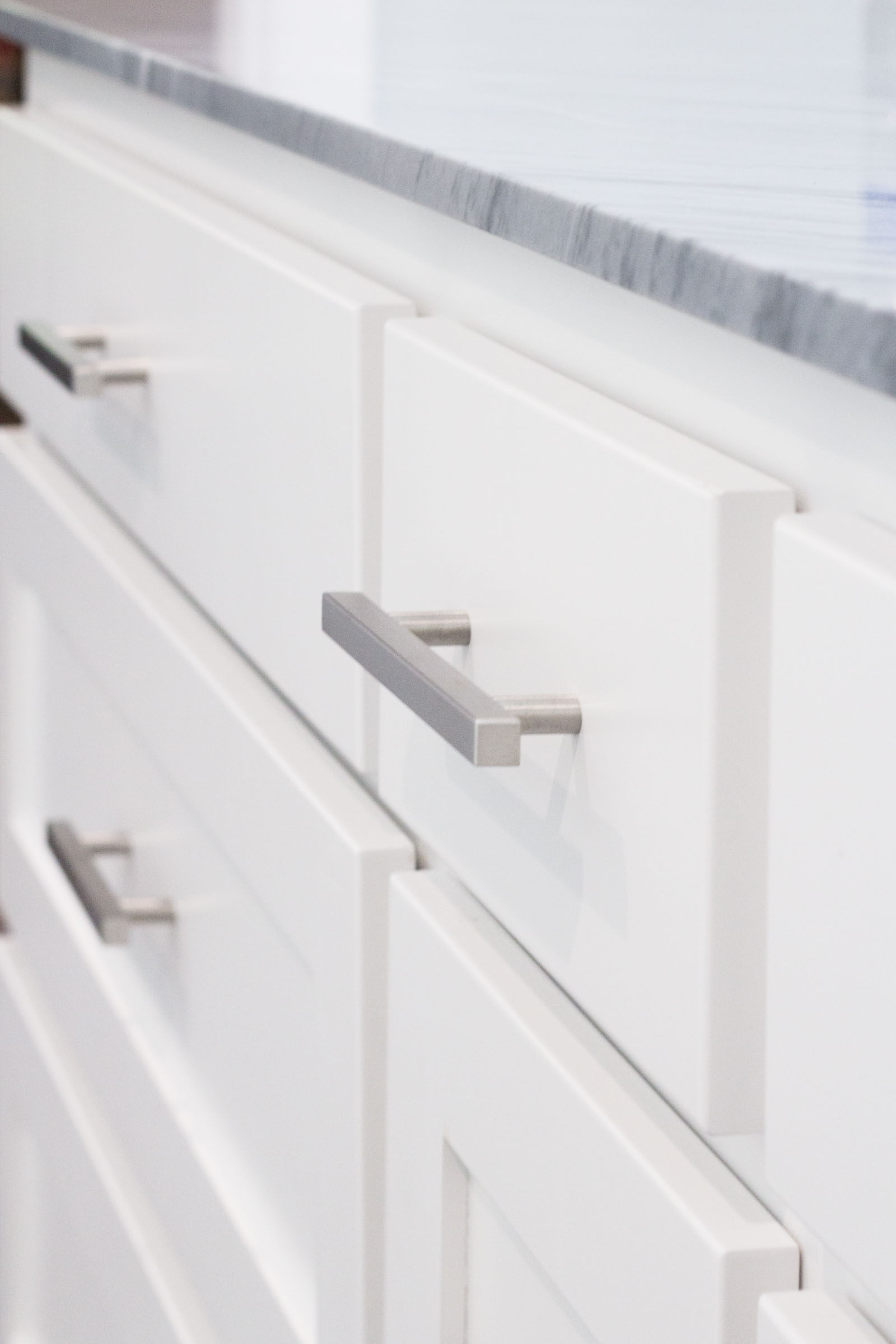 White shaker style bathroom cabinets with grey granite countertop and matte silver hardware