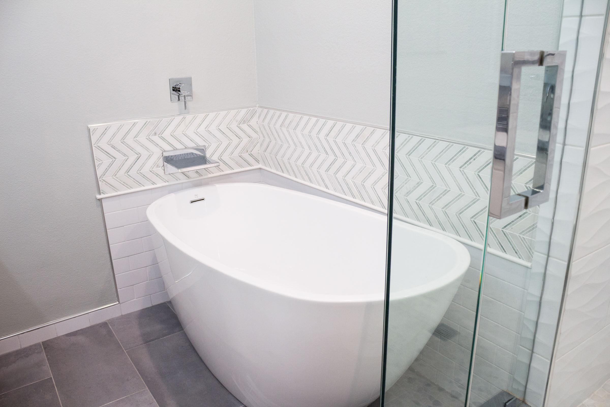Bathroom remodel with white pedestal tub, chevron backsplash, grey tile, and chrome waterfall faucet