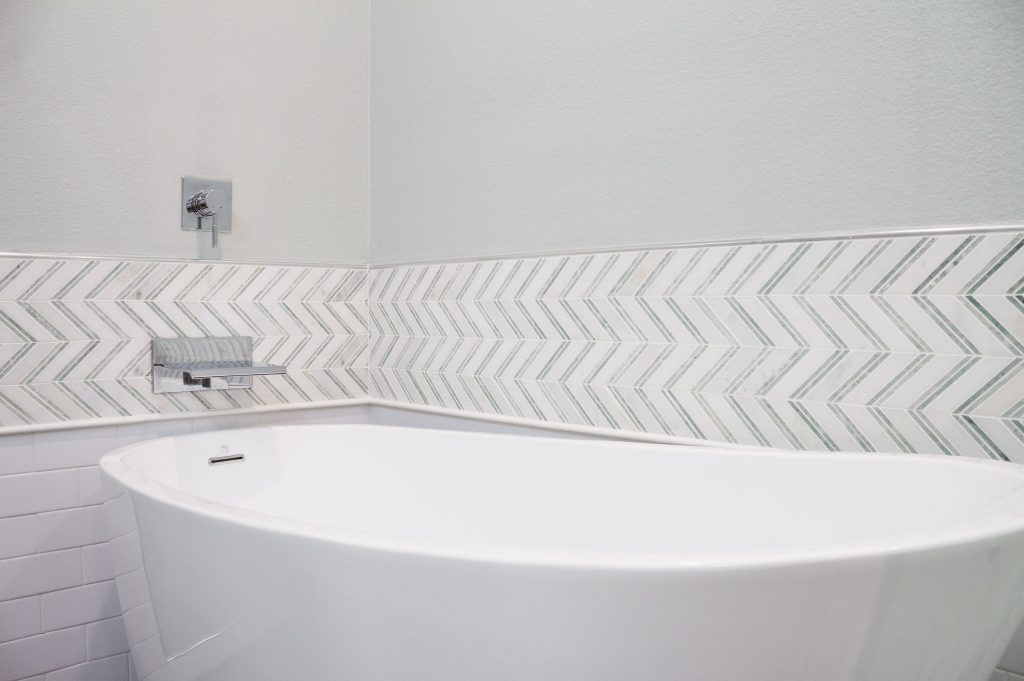 Pedestal bathtub with chevron backsplash and waterfall faucet