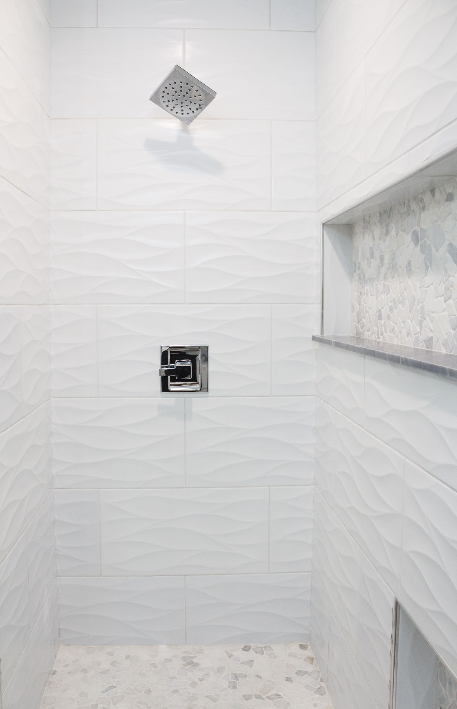 White walk in shower remodel with tile variety and stainless steel hardware