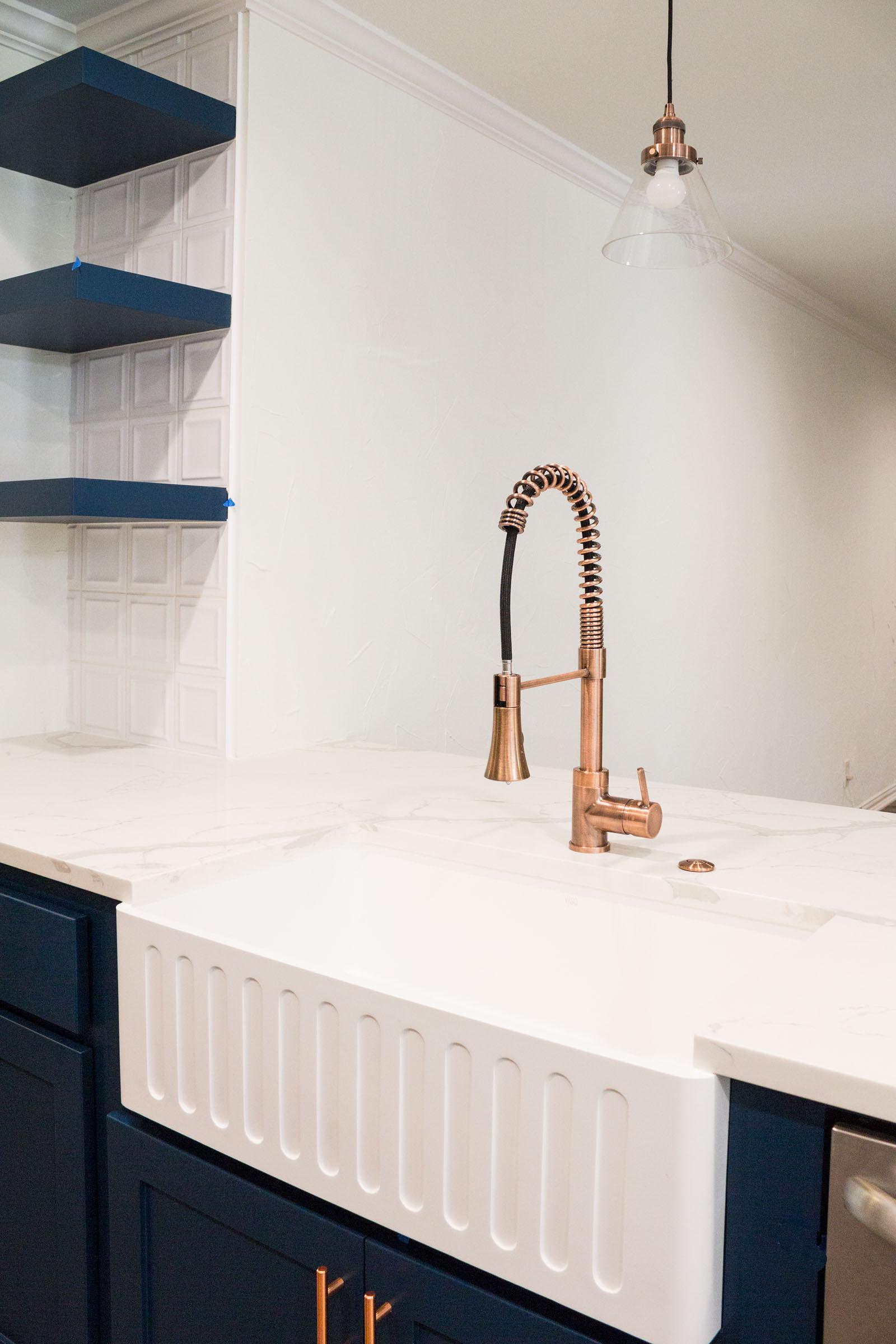 Navy floating shelves, white square backsplash tiles, white granite, copper accents