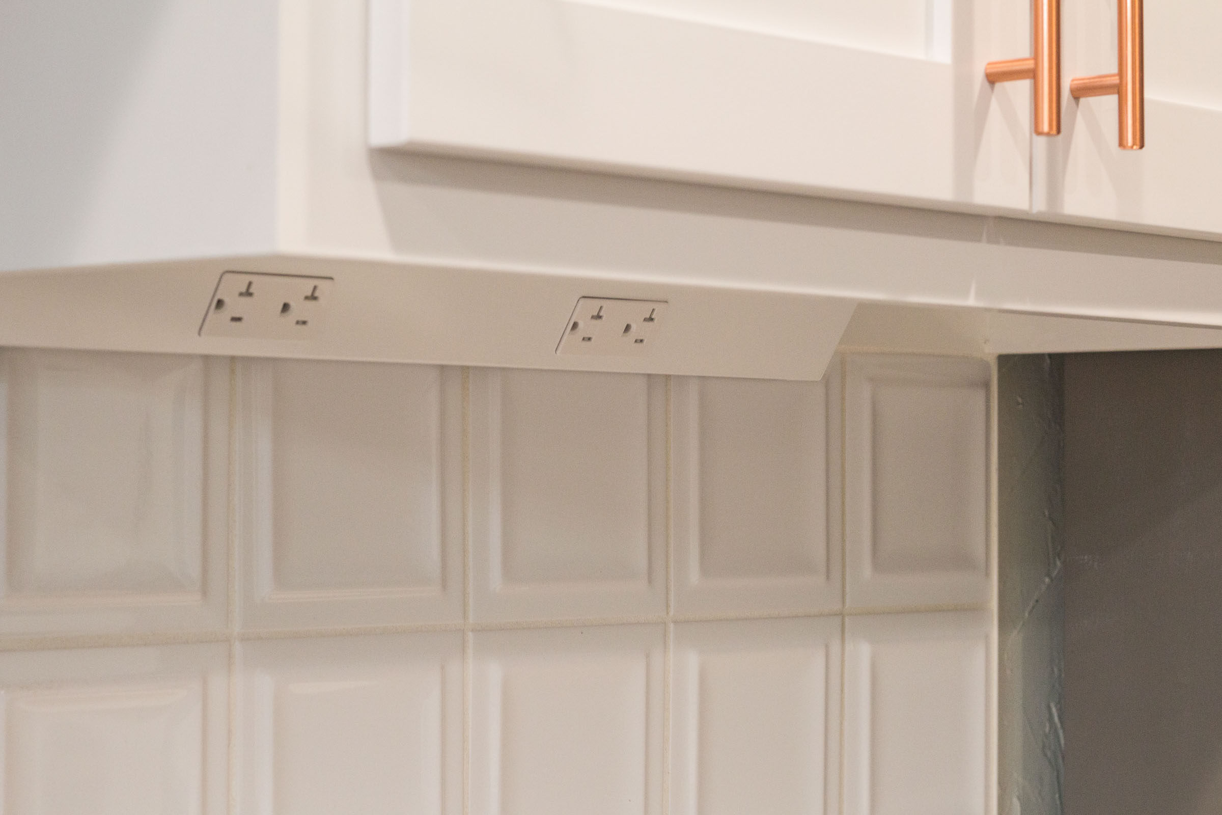 Under cabinet outlets, kitchen appliance electricity, white backsplash, copper cabinet hardware