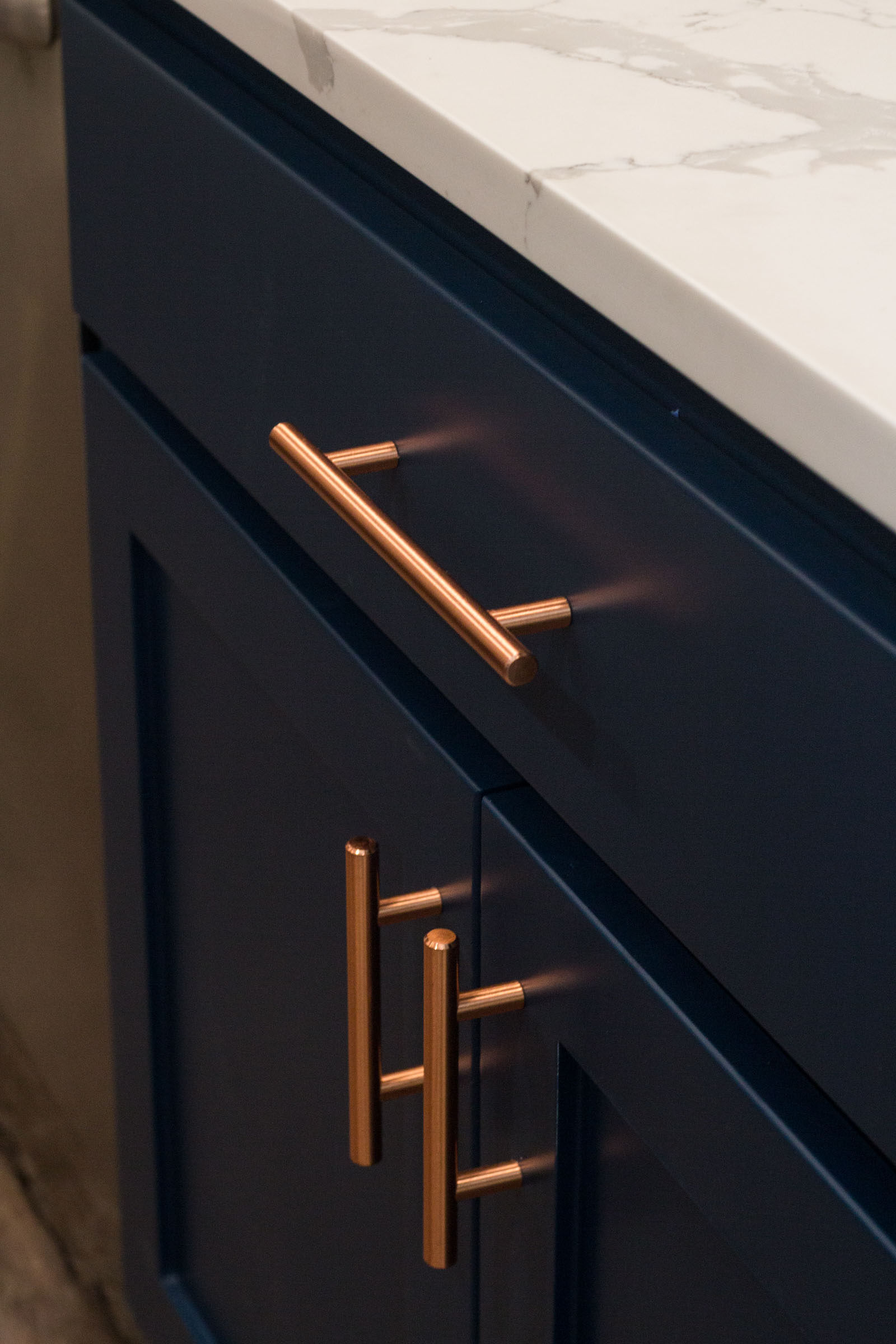 Close up of navy cabinets and copper hardware with white marble style counters