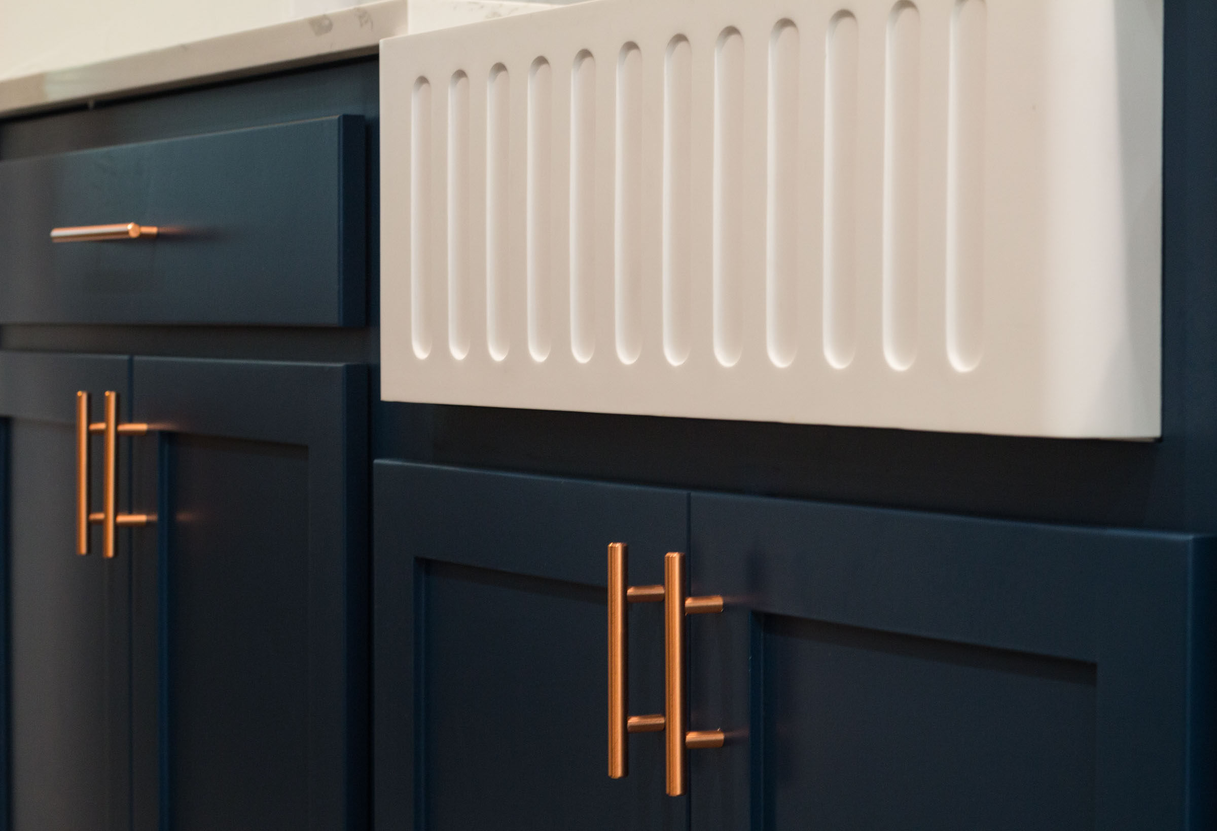 Close up of navy cabinets, copper hardware, and white farmhouse sink with grooves
