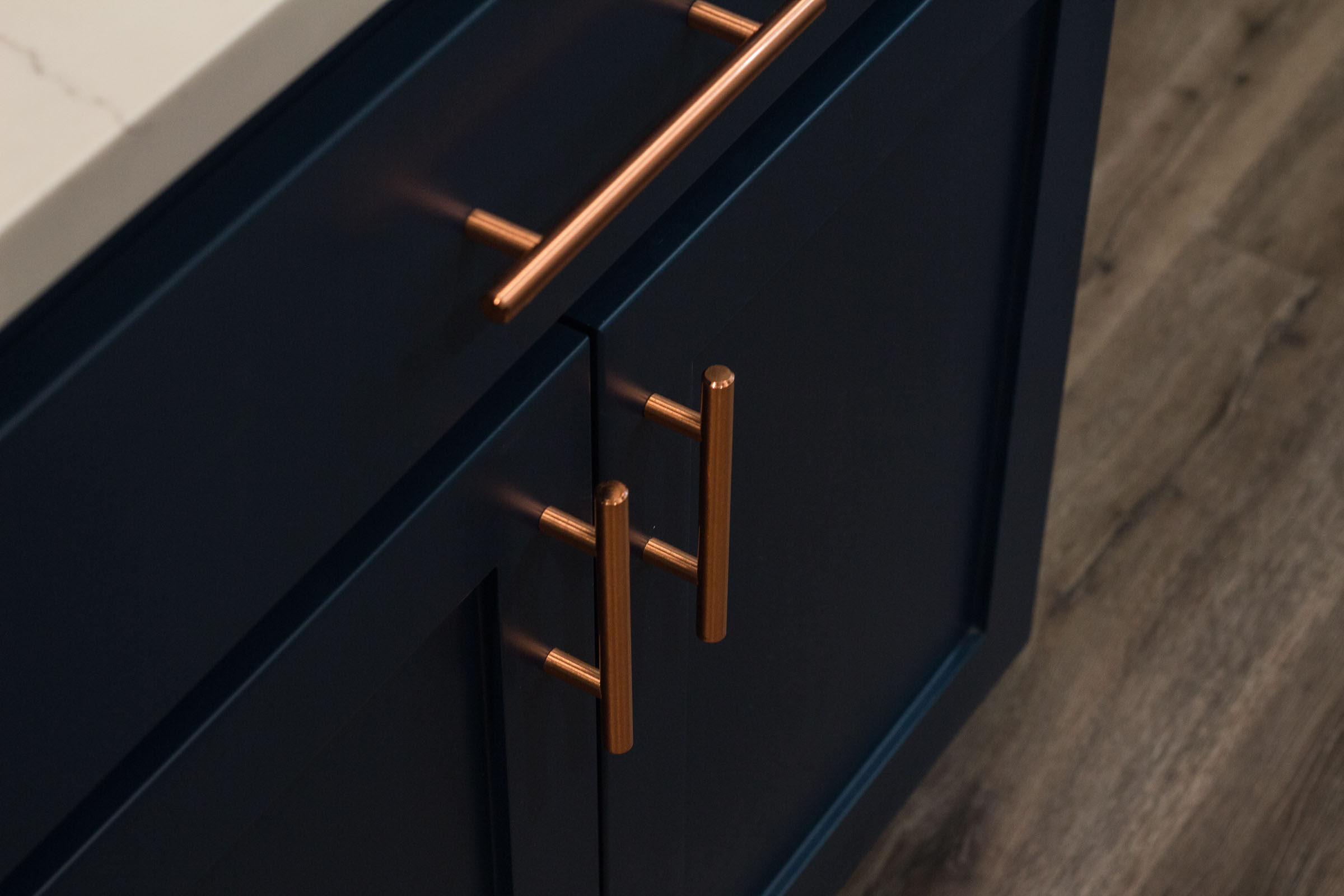 Close up of navy lower cabinets and copper drawer pulls