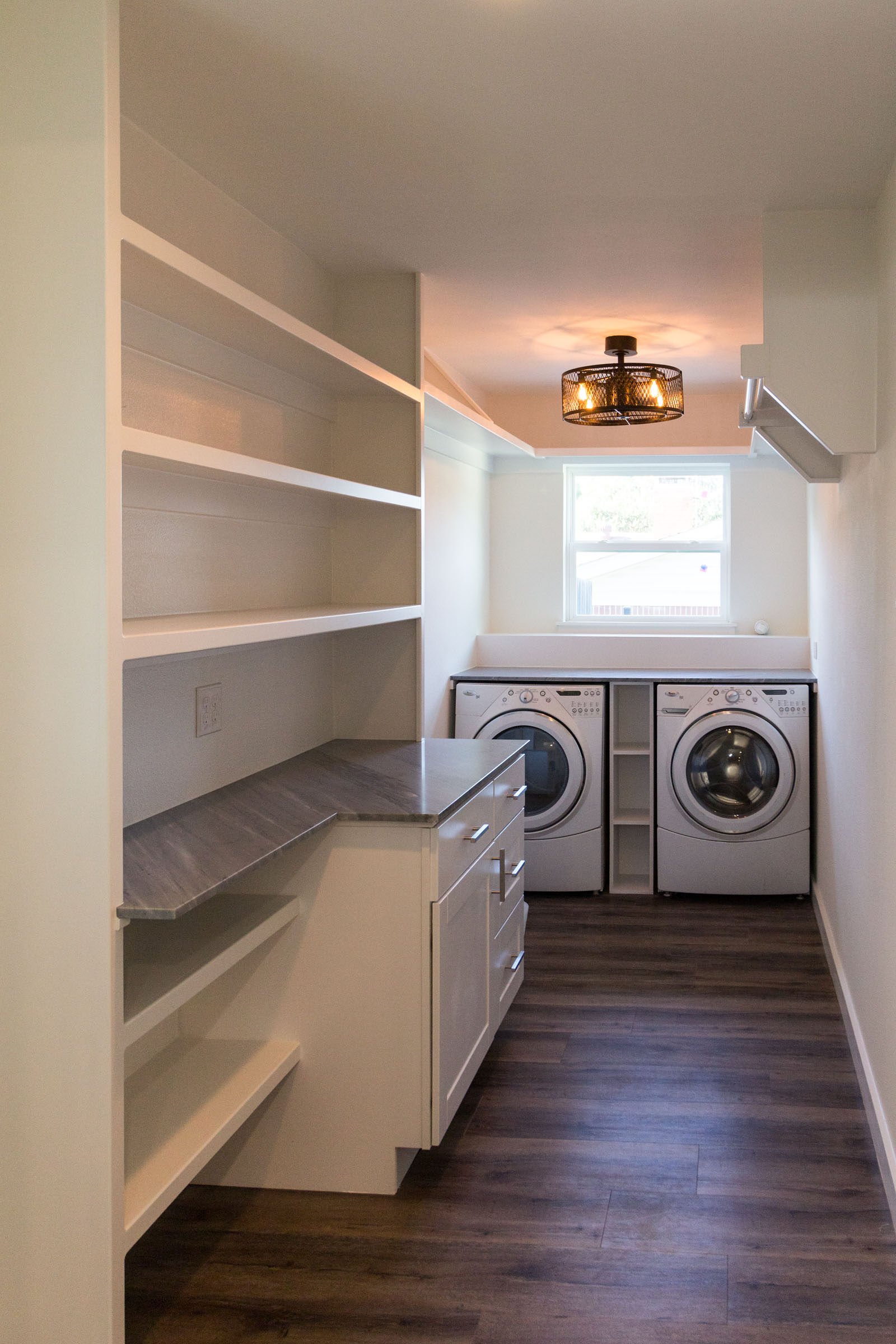 Laundry room built in shelves with folding counter and wood floors