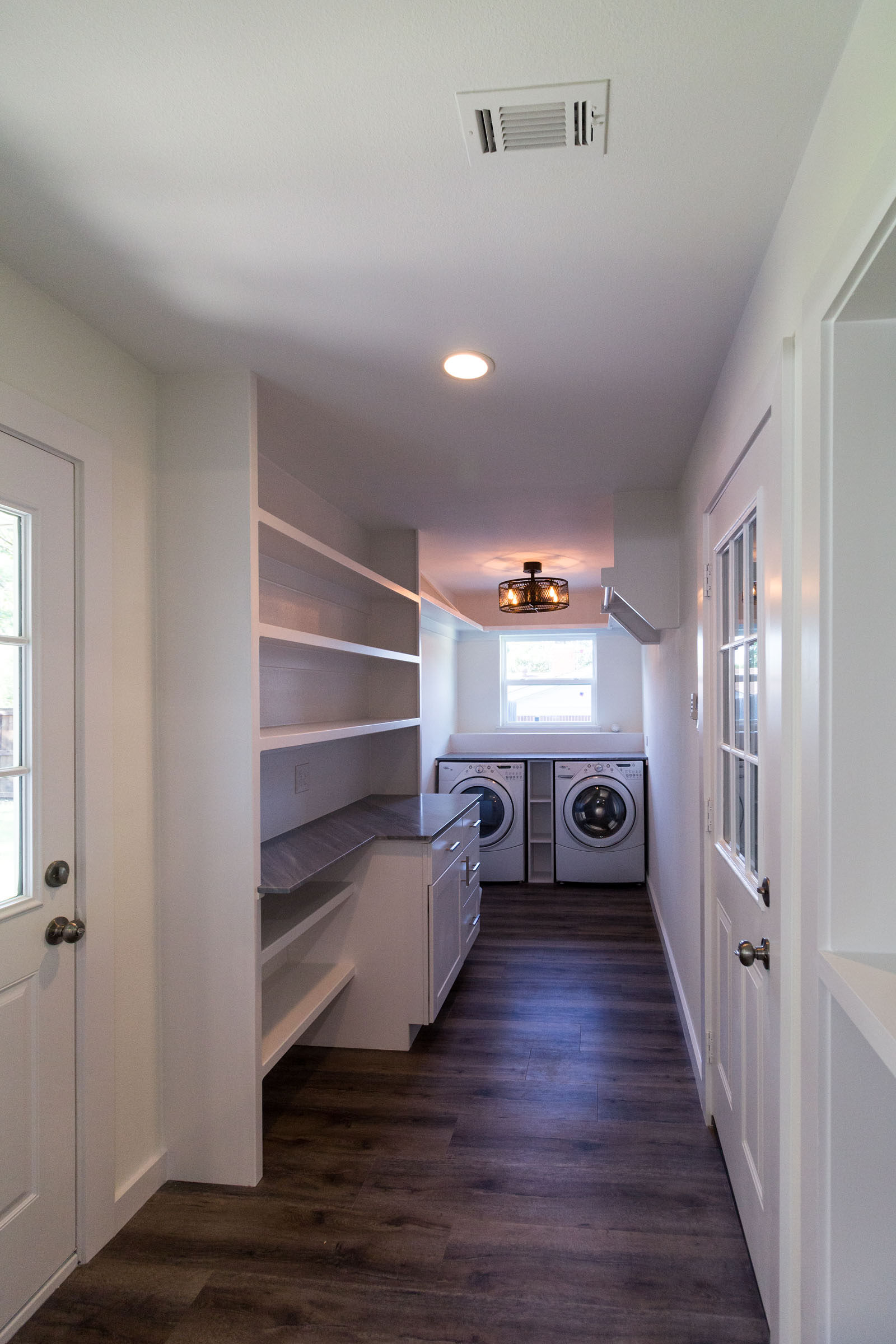 Mud room and laundry room remodel with built in shelves and white walls