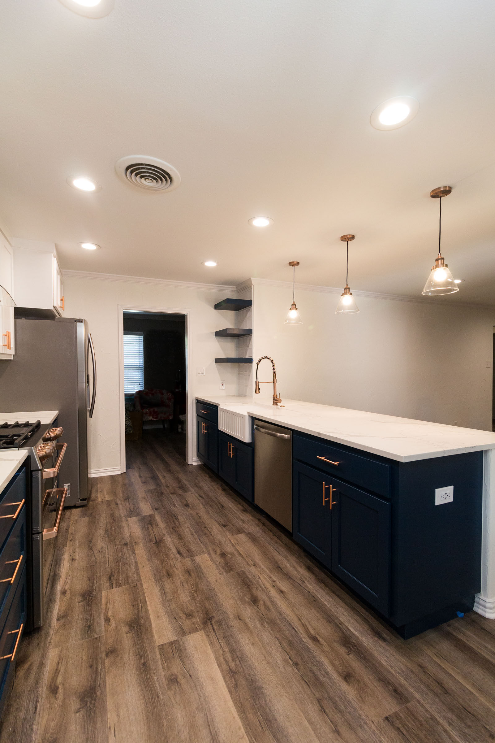 Navy cabinets with copper hardware and white granite