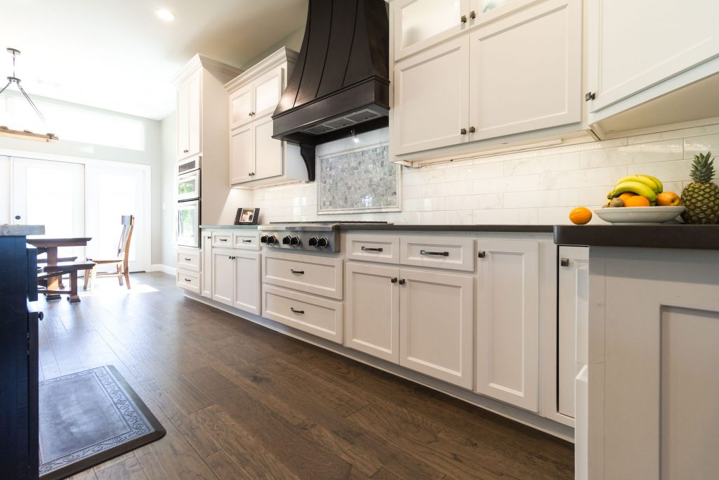 Custom kitchen, shaker style cabinets, espresso vent hood, backsplash, hardwood flooring, fruit, black granite, grey and white neutral color scheme